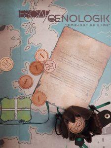 une bourse avec des pièces en bois gravées sont déposées sur le plateau de jeu escap'oenologik
