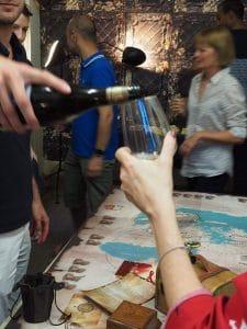 plusieurs joueurs autour du plateau de jeu escap'oenologik un homme sert un verre de vin