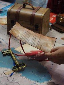 une lettre parchemin tenue par une main féminine une grosse clé ancienne posée tout près