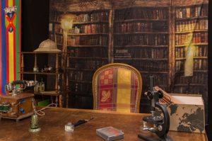 le bureau d'un explorateur est mis en scène avec un grand fauteuil coloré près d'un bureau, sur celui-ci un téléphone, un téléscope et un chapeau d'explorateur