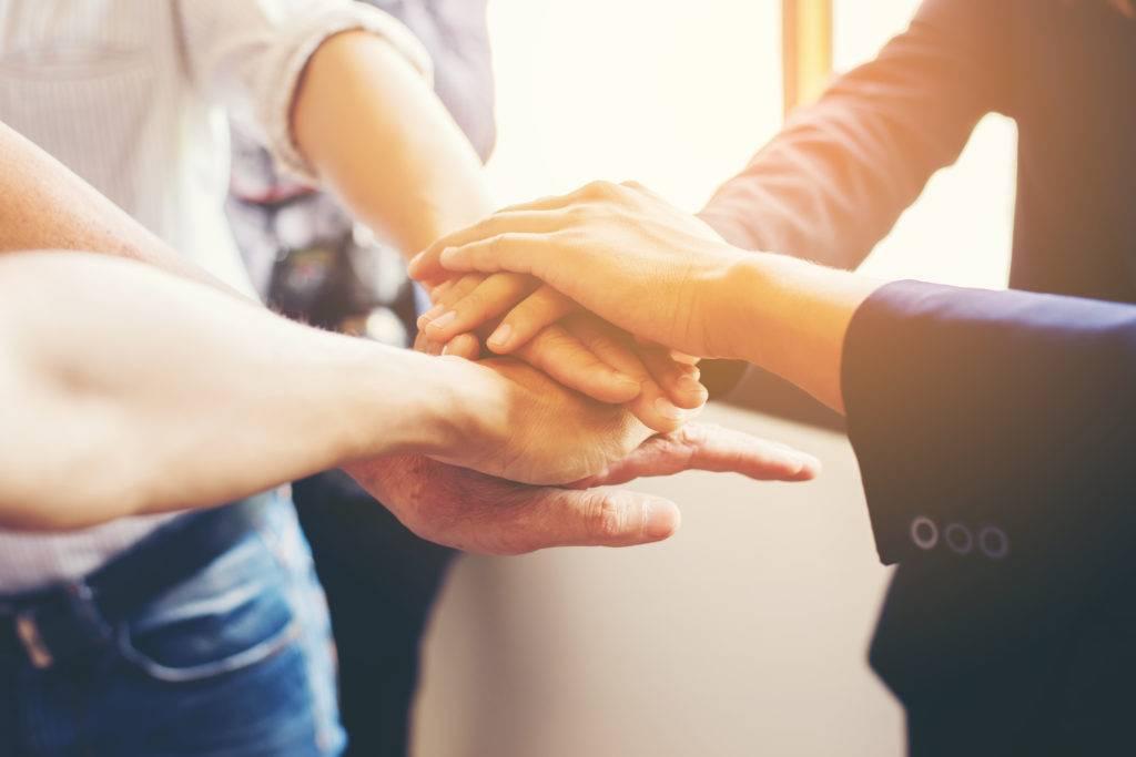 des personnes rassemblent leurs mains pour montrer leur cohésion