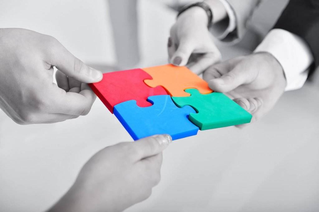 4 mains tiennent une pièce de puzzle de couleur à emboiter