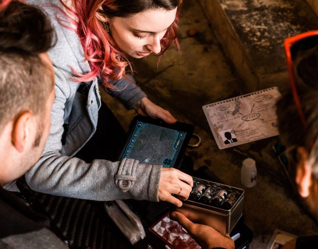 3 joueurs manipulent des objets fioles médicales une tablette tactile