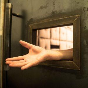 un prisonnier passe une main à travers le passe-plat de sa cellule