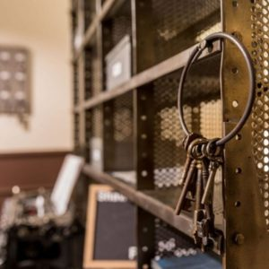 un gros trousseau de clés anciennes accrochées à un casier de prison en fer, en arrière plan une machine à écrire