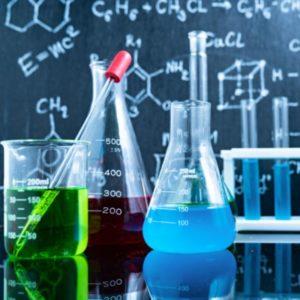 devant un tableau noir où sont inscrits des formules scientifiques à la craie, des béchers et récipients sont remplis de produits colorés rouge, vert et bleu