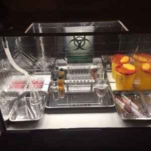 boîte de manipulation de produits chimiques dangereux, une pancarte écrite en russe, une boîte de déchets infectieux, des seringues remplies de sang, un becher, un porte tube à essais