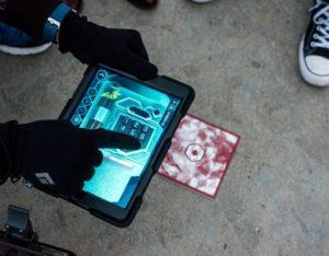 des mains d'hommes gantées manipulent une tablette éléctronique
